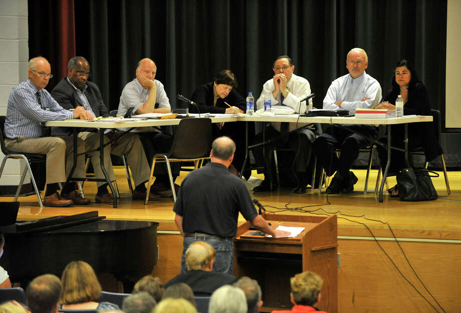 Michael Gorman, center at podium, speaks before the Stamford Planning Board during the public hearing at Westover Elementary School in Stamford on Tuesday, Aug. 20, 2013. The hearing is dealing with the relocation of a boatyard in order to bring hedge fund giant Bridgewater Associates to the south end. Photo: Jason Rearick / Stamford Advocate