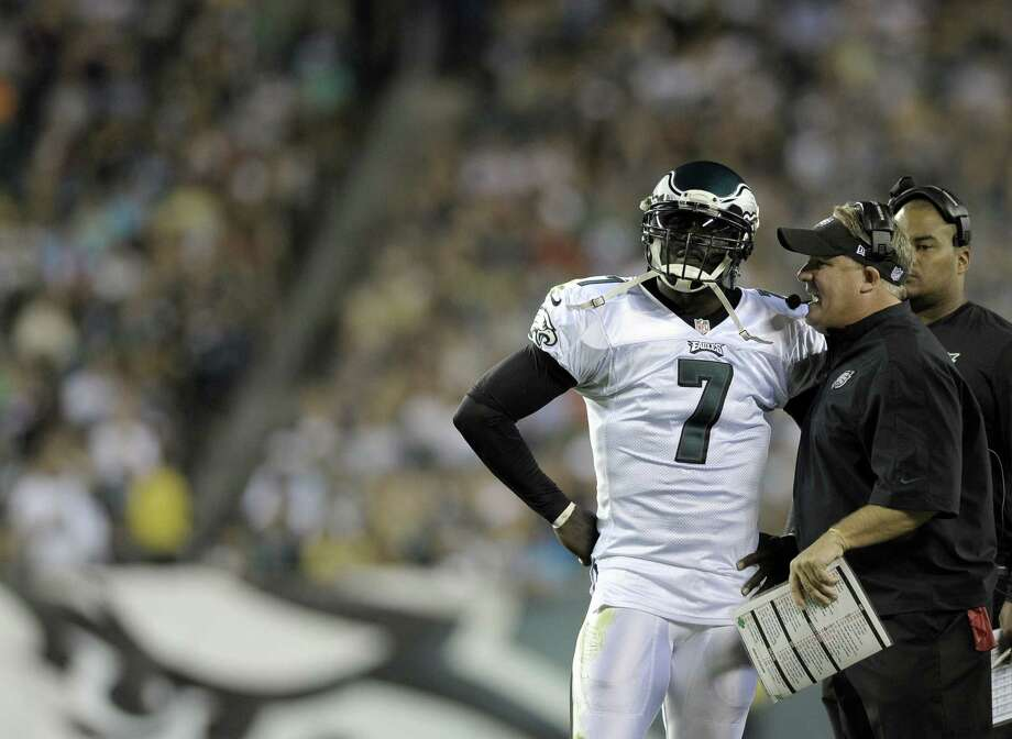 First-year Eagles coach Chip Kelly (center) says QB Michael Vick (7) is ahead of Nick Foles at this point. Photo: Michael Perez / Associated Press