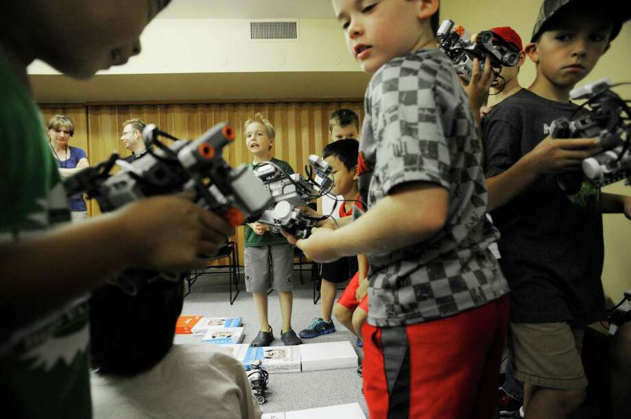 Children line up with robots in hand to try to see if their robot can successfully run through a maze during a Lego Robotics camp at miSci, Museum of Innovation and Science on Tuesday morning, Aug. 20, 2013, in Schenectady, N.Y.  The children in the camp learned programing as they worked in teams to program a robot to run through a maze.  Instructors from Union College and SUNY Albany along with museum staff worked with the children.  Organizers said that the camp gives children the hands on process of solving problems using technology.  This is the first summer in a few years that the museum has run week-long camps throughout the summer.  William Sudduth, executive director of the museum said that plans are already being made for camps next summer. (Paul Buckowski / Times Union) Photo: Paul Buckowski / 00023572A
