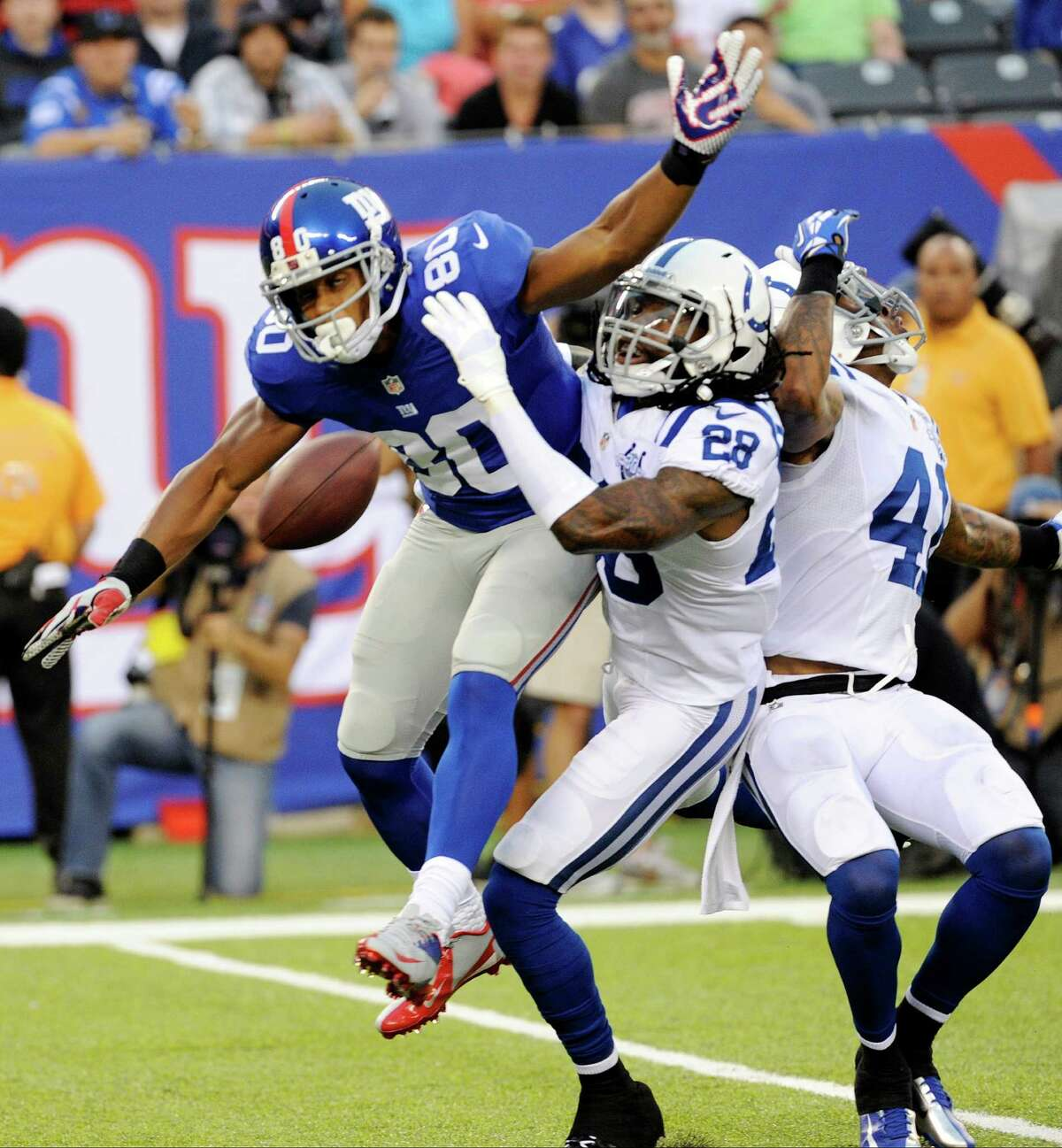 Indianapolis Colts cornerback Greg Toler (28) and Antoine Bethea (41) defend against New York Giants wide receiver Victor Cruz (80) during the first half of an NFL preseason football game on Sunday, Aug. 18, 2013, in East Rutherford, N.J. Pass interference was called on the play. (AP Photo/Bill Kostroun) ORG XMIT: ERU102