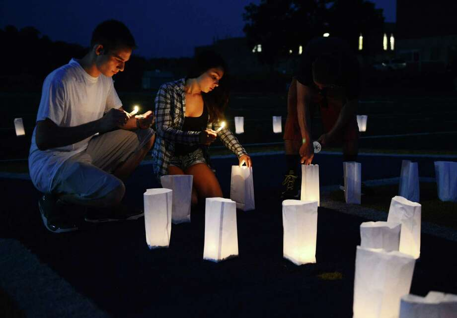 Will Baermann and Chantel Pereira, of Brookfield, light candles in remembrance of their friend Jose Schelmetty at the candlelight vigil held in his memory at Brookfield High School in Brookfield, Conn. on Tuesday, Aug. 20, 2013.  Schelmetty died suddenly and unexpectedly on Sunday and hundreds gathered to participate in the vigil Tuesday. Photo: Tyler Sizemore / The News-Times