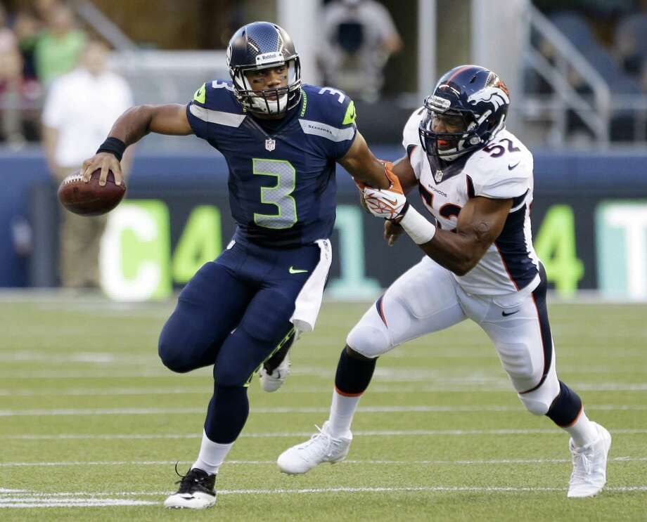 Seattle Seahawks quarterback Russell Wilson (3) scrambles while being chased by Denver Broncos' Wesley Woodyard in the first half of a preseason NFL football game, Saturday, Aug. 17, 2013, in Seattle. (AP Photo/Elaine Thompson) ORG XMIT: SEA129 Photo: Elaine Thompson / AP