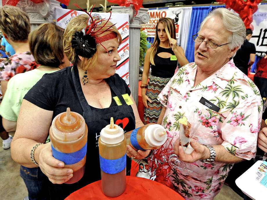 Lisa McLemore, left, questions John Alden Hughes Wright, right, on which homemade sauce he wants with his Red Carpet Ribs from the Apartment Association of Southeast Texas during the 11th Annual Tasting for Some Other Place at the Civic Center on Tuesday, August 20, 2013. Photo taken: Randy Edwards/The Enterprise Photo: Randy Edwards, Photojournalist / Enterprise