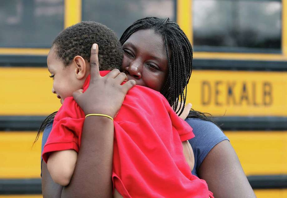LaTrease Akins hugs her 5-year-old son Mark Wheeler after being reunited following a shooting incident at McNair Discovery Learning Academy Tuesday, Aug. 20, 2013 in Decatur, Ga.  A teen opened fire with an assault rifle Tuesday at officers who shot back at the Atlanta-area elementary school, the police chief said, with dramatic overhead television footage capturing the young students racing out of the building, being escorted by teachers and police to safety. No one was injured. (AP Photo/Atlanta Journal-Constitution, Ben Gray)  MARIETTA DAILY OUT; GWINNETT DAILY POST OUT; LOCAL TV OUT; WXIA-TV OUT; WGCL-TV OUT ORG XMIT: GAATJ301 Photo: Ben Gray / Atlanta Journal-Constitution