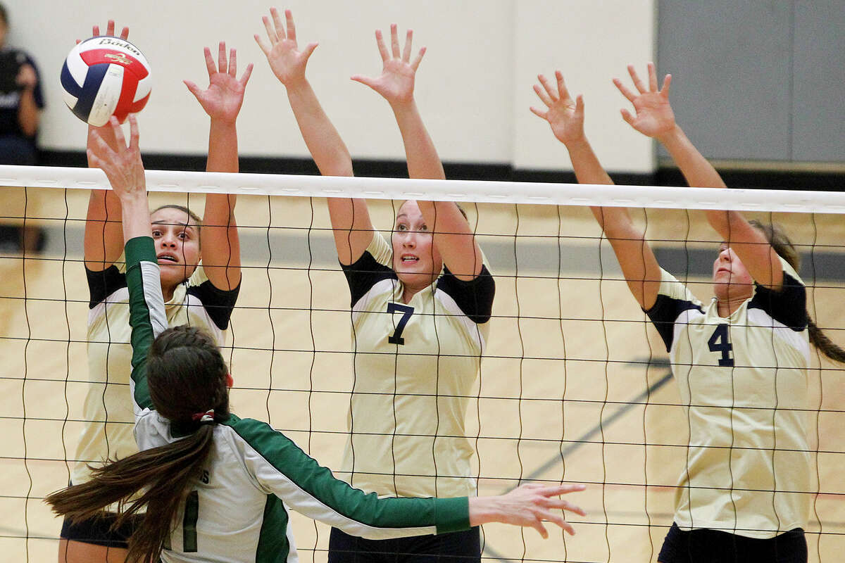 O'Connor's Gillianne Simpkins (from left) Laura Fox and McKenzie Kelley try to block a shot by Reagan's Ashlie Reasor during their match at Littleton Gym on Tuesday, Aug. 20, 2013. Reagan won the match in three straight sets, 25-17, 25-21 and 25-22. MARVIN PFEIFFER/ mpfeiffer@express-news.net