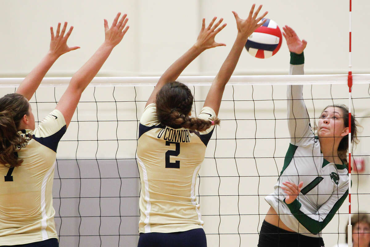 Reagan's Krista Kolbinskie (from right) tries to get a shot past O'Connor's Alex Ecker and McKenzie Kelley during their match at Littleton Gym on Tuesday, Aug. 20, 2013. Reagan won the match in three straight sets, 25-17, 25-21 and 25-22. MARVIN PFEIFFER/ mpfeiffer@express-news.net