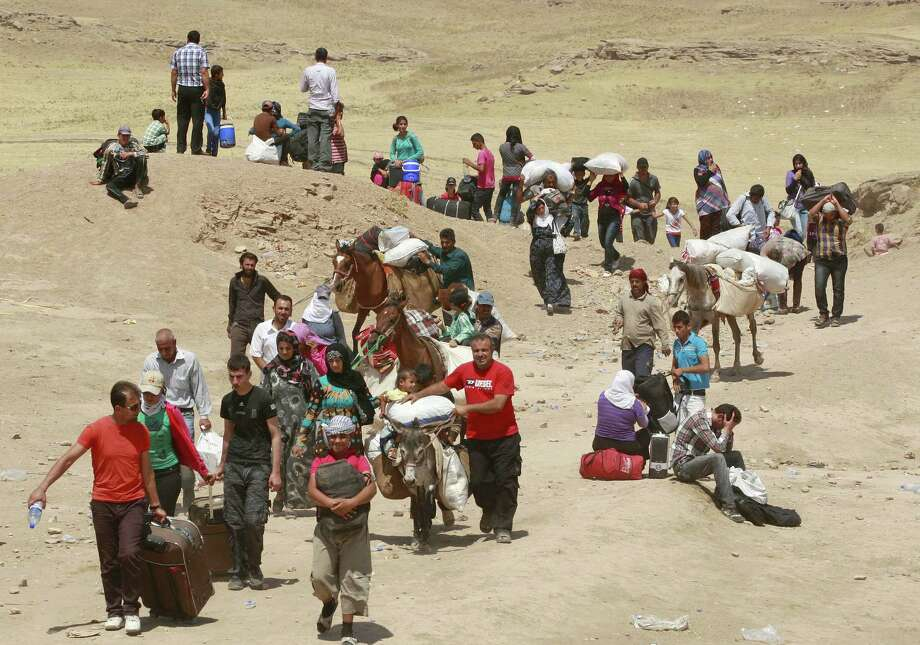 Syrian refugees cross into Iraq at the Peshkabour border point about 260 miles northwest of Baghdad. Some 30,000 Syrians, the vast majority of them Kurds, have fled the region over a five-day stretch. Photo: Hadi Mizban / Associated Press
