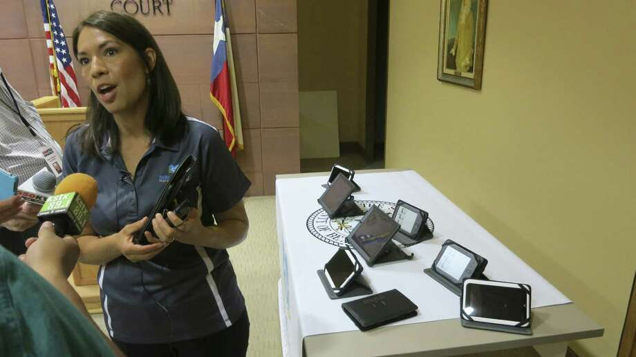 BiblioTech branch manager Catarina Velasquez demonstrates e-reader devices that will be available when the library opens Sept. 14. Photo: John W. Gonzalez / San Antonio Express-News