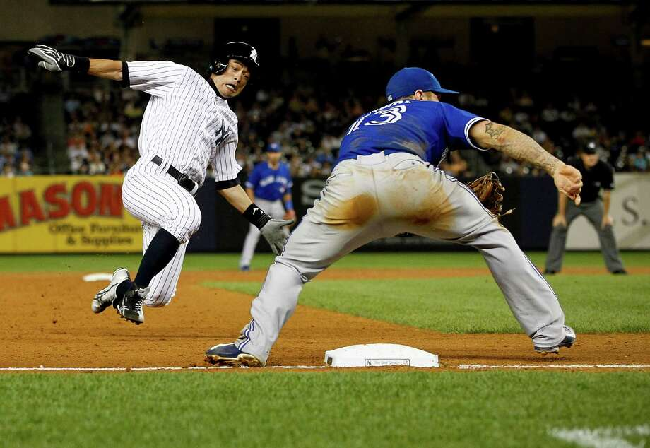 NEW YORK, NY - AUGUST 20:  Ichiro Suzuki #31 of the New York Yankees steals third base ahead of a throw to Brett Lawrie #13 of the Toronto Blue Jays during the second game of a double header at Yankee Stadium on August 20, 2013 in the Bronx Borough of New York City.  (Photo by Jeff Zelevansky/Getty Images) ORG XMIT: 163495100 Photo: Jeff Zelevansky / 2013 Getty Images