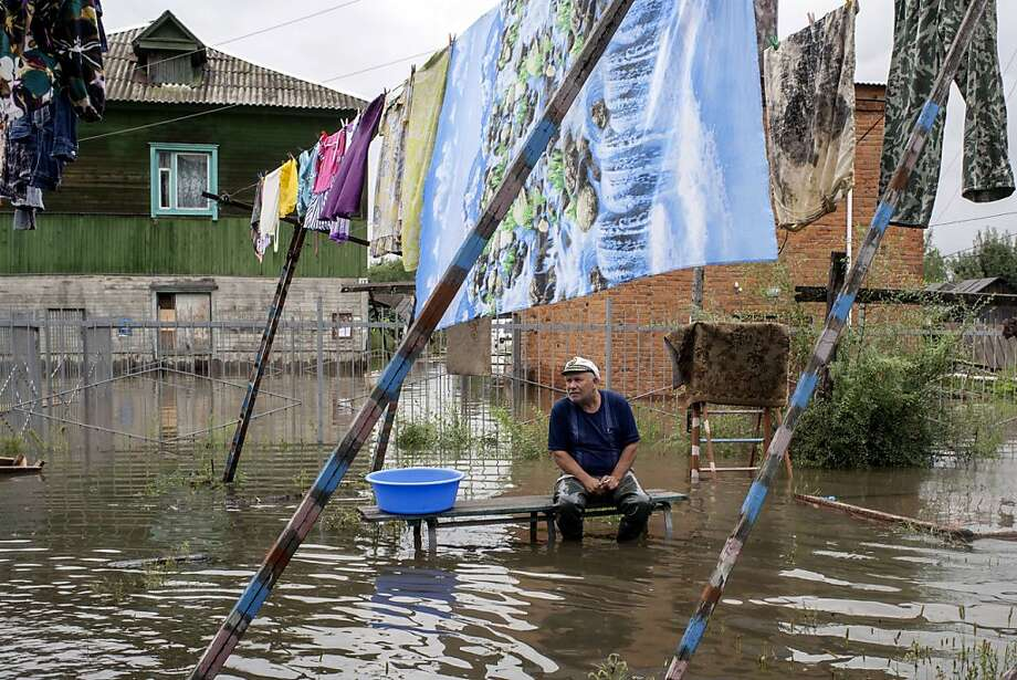 TOPSHOTS A man sits on a bench as clothes are hung to dry in a flooded street in the village of Bolshoi Ussuriysky island close to city of the Khabarovsk in Russia's Far Eastern Amur region, on August 19, 2013. Russians in the Far East battled rising floodwaters as authorities evacuated more than 23,000 people from affected areas and scrambled to prevent the outbreak of infection. Heavy rains pounding Khabarovsk, a Far Eastern city located near the Chinese border, since July have swelled the local Amur River to nearly 7 meters -- a level unseen since monitoring of the area began in 1895.  AFP PHOTO/IGOR CHURAKOVIGOR CHURAKOV/AFP/Getty Images Photo: Igor Churakov, AFP/Getty Images