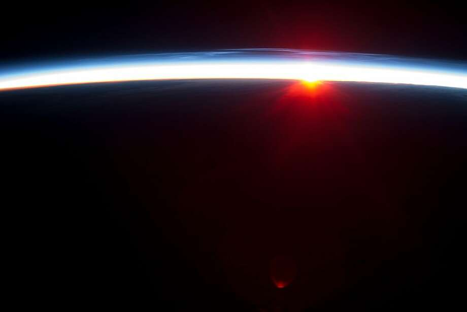 """This NASA panoramic photo released August 20, 2013, was taken by Astronauts on the International Space Station (ISS)  looking northeast from a point half-way along the Aleutian Island chain. They were flying east at the top of the orbitthe northernmost latitude reached by the ISS (51.6 degrees north). If the Sun had been higher, western Alaska would have been visible in the foreground; instead, it lies on the dark side of the day-night line. This image was taken about 15 minutes after local midnight in early August 2013. From their vantage point at 222 kilometers altitude, the astronauts were able to look northeast and see a near-midnight sunrise (when it was approaching noon in England). The rising Sun makes a red, teardrop-shaped reflection in the lower center of the imageperhaps a reflection within the camera lens, from the window frame, or from some item inside the spacecraft. Long, blue-white ripples appear in the atmosphere above the midnight sun. These are noctilucent or night-shining clouds. Some astronauts say these wispy, iridescent clouds are the most beautiful phenomena they see from orbit.  AFP PHOTO / NASA/ISS == RESTRICTED TO EDITORIAL USE / MANDATORY CREDIT: """"AFP PHOTO / NASA/ISS / NO MARKETING / NO ADVERTISING CAMPAIGNS / DISTRIBUTED AS A SERVICE TO CLIENTS ==HO/AFP/Getty Images Photo: Ho, AFP/Getty Images"""