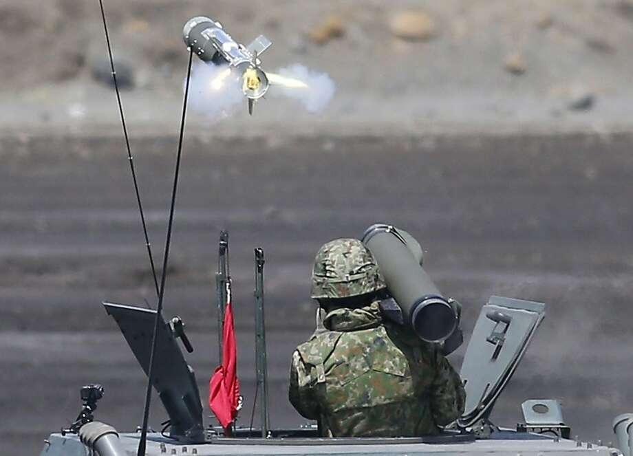 A Japan Ground Self-Defense Force soldier launches a hand-held anti-tank rocket during an annual live firing exercise at Higashi Fuji range in Gotemba, southwest of Tokyo, Tuesday, Aug. 20, 2013. (AP Photo/Koji Sasahara) Photo: Koji Sasahara, Associated Press