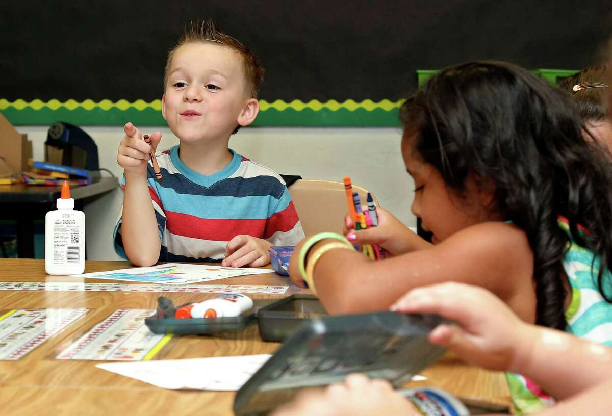 First-grade student Conner Lewis, left, talks with his classmates as they draw on the first day of school for Plaza Towers Elementary school in their temporary location in Central Jr. High school in Moore, Okla., Friday, Aug. 16, 2013. The Briarwood and Plaza Towers elementary schools were destroyed when an EF5 twister hit Moore on May 20, killing seven students. (AP Photo/Sue Ogrocki)
