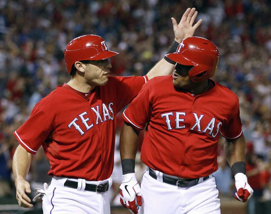 The Rangers' Adrian Beltre (right) is greeted by teammate Ian Kinsler after delivering a go-ahead, two-run homer in the sixth inning against the Astros. Photo: Jim Cowsert / Associated Press