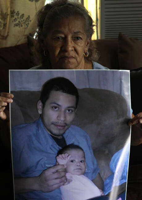 Stella Lopez holds a photo of grandson Gilbert Ramos, 25, who was killed as he walked while carrying his laundry along South General McMullen Drive. The little girl being held by Ramos in the photo is his daughter Azeriyah Huichan. Photo: John Davenport / San Antonio Express-News