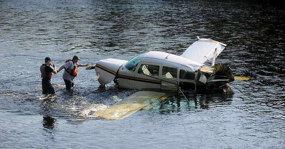 Charles Robins, right, of Charlie and Sons garage, and Chad Robertson, left, with the Maine Warden's Service prepare to haul a single engine Beechcraft airplane from the Kennebec River after it crashed on take-off from Gadabout Gaddis Airport in Bingham, Maine, on Tuesday, Aug. 20, 2013. The two men aboard, owner Ray Ayer, 59, of Monmouth, and Paul Householder, 54, of Wayne, were unhurt, police said. (AP Photo/The Central Maine Morning Sentinel, Michael G. Seamans) Photo: Michael G. Seamans, Associated Press