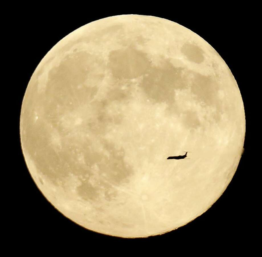 A plane cruises in front of the moon in its full stage under a phenomenon called the blue moon, as seen from West Orange, N.J., Tuesday, Aug. 20, 2013. The moon is the third moon of four in the summer season, better known as a blue moon to scientists. (AP Photo/Julio Cortez) Photo: Julio Cortez, Associated Press
