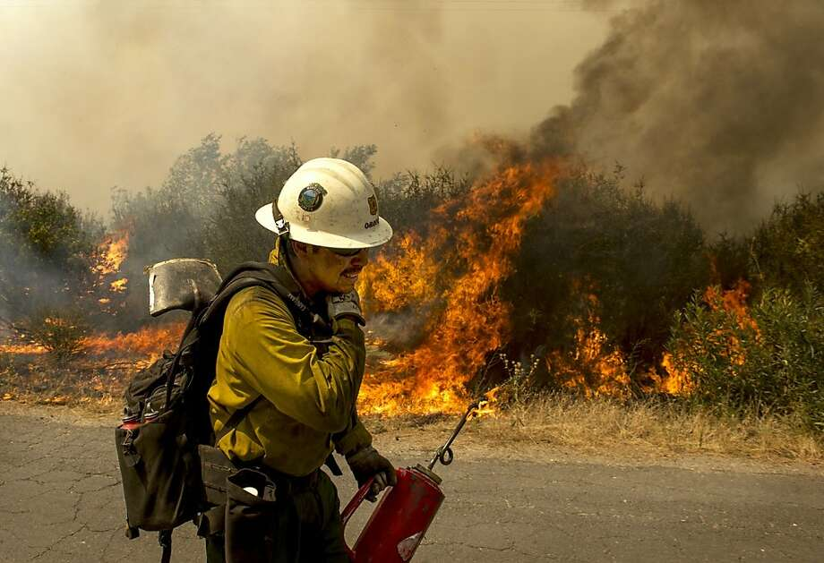 A U.S. Forest Service firefighter moves away from a quickly moving section of the Rim Fire in the Stanislaus National Forest Tuesday, Aug. 20, 2013. (AP Photo/The Modesto Bee, Andy Alfaro) LOCAL TV OUT (KXTV10, KCRA3, KOVR13, FOX40, KMAX31, KQCA58, CENTRAL VALLEY TV); LOCAL PRINT OUT (TURLOCK JOURNAL, CERES COURIER, OAKDALE LEADER, MODESTO VIEW, PATTERSON IRRIGATOR, MANTECA BULLETIN, RIPON, RECROD, SONORA UNION DEMOCRAT, AMADOR LEDGER DISPATCH, ESCALON TIMES, CALAVERAS ENTERPRISE, RIVERBANKS NEWS) LOCAL INTERNET OUT (TURLOCK CITY NEWS.COM, MOTHER LODE.COM) Photo: Andy Alfaro, Associated Press