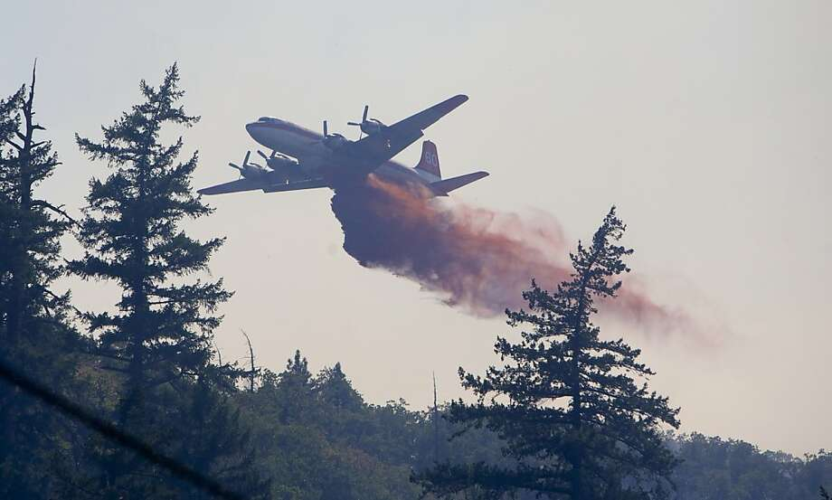 A tanker drops retardant along a fire line on the Blackburn fire, just above the city of The Dalles, Ore. water treatment plant Tuesday afternoon, Aug. 20, 2013. Firefighters below the plant were back-burning to create a safe zone for the facility. The fire continued to spread through timberlands, ranches and orchards interspersed with canyons on the northern flanks of Mount Hood. (AP Photo/The Oregonian, Randy L. Rasmussen)  MAGS OUT; TV OUT; LOCAL TV OUT; LOCAL INTERNET OUT; THE MERCURY OUT; WILLAMETTE WEEK OUT; PAMPLIN MEDIA GROUP OUT Photo: Randy L. Rasmussen, Associated Press