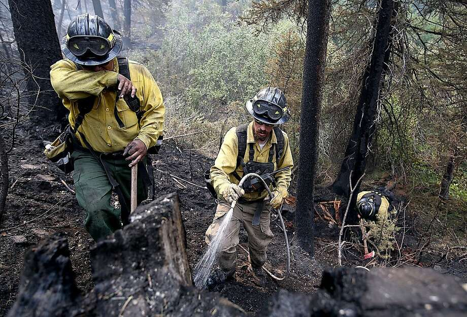 In this Monday, Aug. 19, 2013 photo, firefighters with the private contract company Great Basin Fire, mop up part of the 104,457-acre Beaver Creek Fire in the Baker Creek area north of Ketchum, Idaho. (AP Photo/Times-News, Ashley Smith) Photo: Ashley Smith, Associated Press