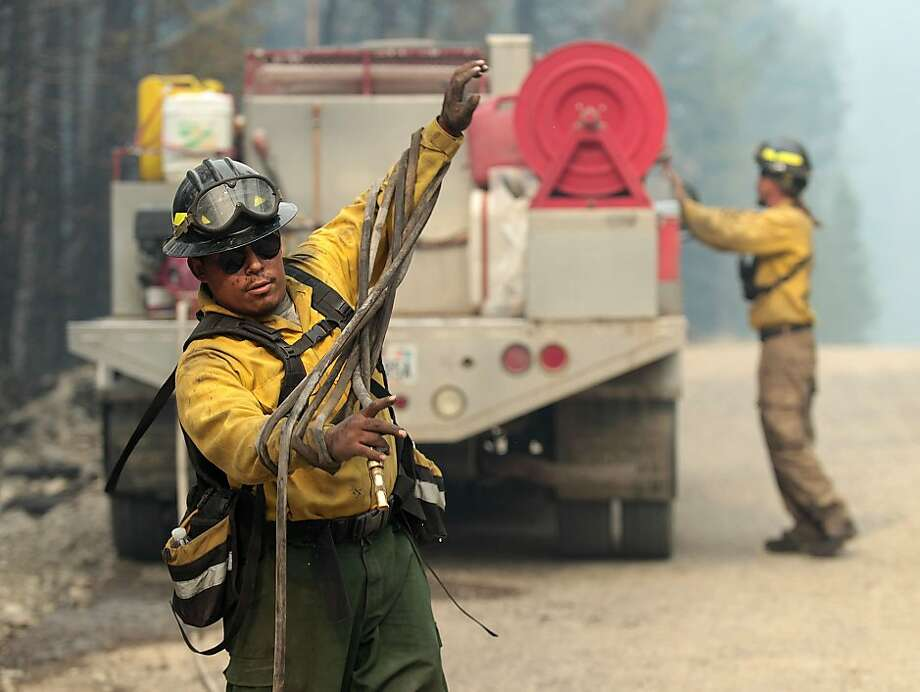 In this Monday, Aug. 19, 2013 photo, firefighters with the private contract company Great Basin Fire, mop up part of the 104,457-acre Beaver Creek Fire in the Baker Creek, north of Ketchum, Idaho. (AP Photo/Times-News, Ashley Smith) Photo: Ashley Smith, Associated Press