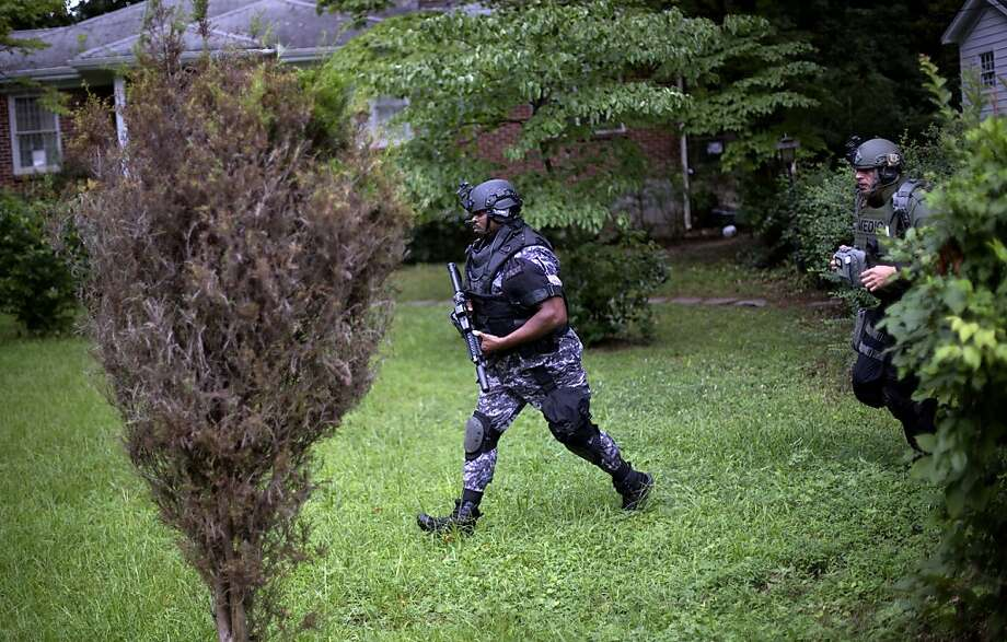 Dekalb County Police SWAT officers run though the front yard of a home toward Ronald E. McNair Discovery Learning Academy after reports of a gunman entered the school, Tuesday, Aug. 20, 2013, in Decatur, Ga.  Superintendent Michael Thurmond says all students at Ronald E. McNair Discovery Learning Academy in Decatur east of Atlanta are accounted for and safe Tuesday and that he is not aware of any injuries. (AP Photo/David Goldman) Photo: David Goldman, Associated Press