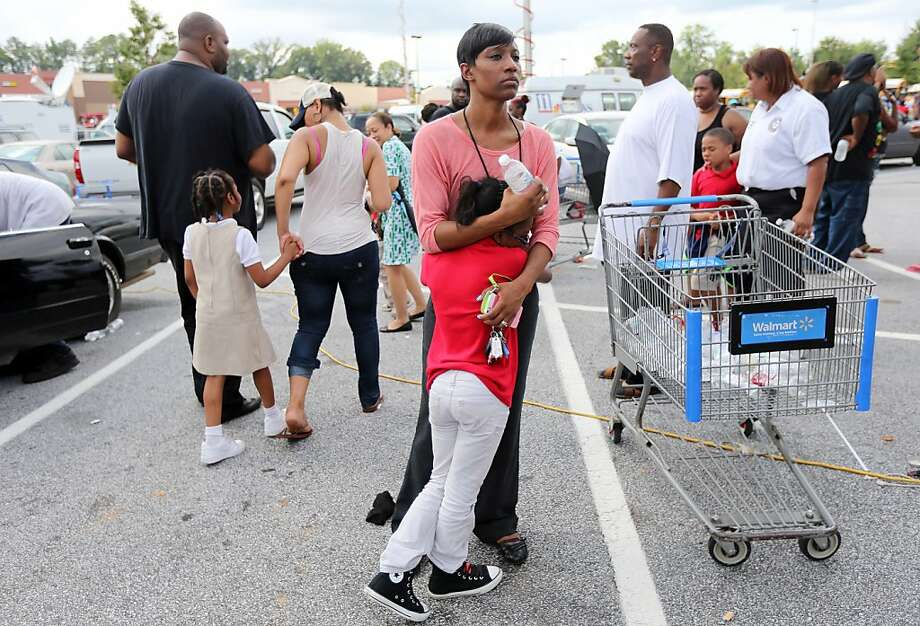 "Keondria Williams holds on tight to her daughter, Kierstin Williams, 8, after they were reunited in a Wal-mart parking lot Tuesday afternoon Aug. 20, 2013 after McNair Discovery Learning Academy in Decatur was evacuated because of a gunman who fired shots from inside the school. Williams, who was waiting for her husband to be reunited with their younger child, said she was probably more scared than her daughter. ""You want to make sure you hug on them, love them and tell them you love them every single day,"" she said of her children. (AP Photo/Atlanta Journal-Constitution, Ben Gray)  MARIETTA DAILY OUT; GWINNETT DAILY POST OUT; LOCAL TV OUT; WXIA-TV OUT; WGCL-TV OUT Photo: Ben Gray, Associated Press"