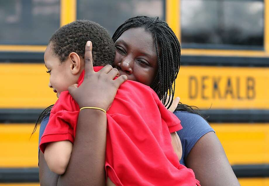 LaTrease Akins hugs her 5-year-old son Mark Wheeler after being reunited following a shooting incident at McNair Discovery Learning Academy Tuesday, Aug. 20, 2013 in Decatur, Ga.  A teen opened fire with an assault rifle Tuesday at officers who shot back at the Atlanta-area elementary school, the police chief said, with dramatic overhead television footage capturing the young students racing out of the building, being escorted by teachers and police to safety. No one was injured. (AP Photo/Atlanta Journal-Constitution, Ben Gray)  MARIETTA DAILY OUT; GWINNETT DAILY POST OUT; LOCAL TV OUT; WXIA-TV OUT; WGCL-TV OUT Photo: Ben Gray, Associated Press