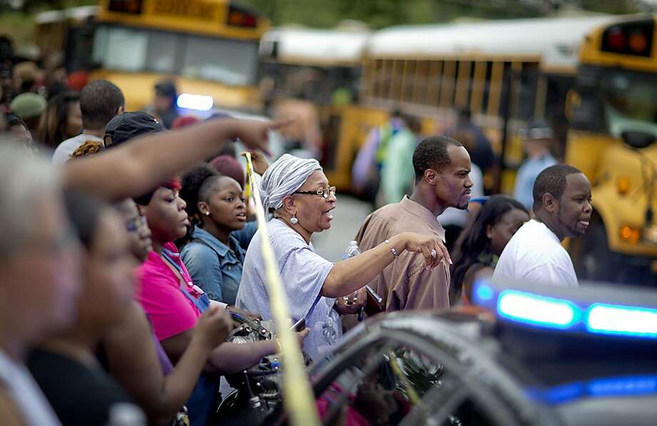Loved ones wait to to be reunited with students from Ronald E. McNair Discovery Learning Academy in a Walmart parking lot after the children and faculty were evacuated when a gunman entered the school, Tuesday, Aug. 20, 2013, in Decatur, Ga. (AP Photo/David Goldman) Photo: David Goldman, Associated Press