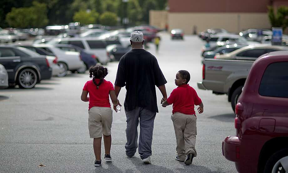 Students from Ronald E. McNair Discovery Learning Academy walk off with a loved one after arriving on school buses to a Walmart parking lot after they were evacuated when a gunman entered the school, Tuesday, Aug. 20, 2013, in Decatur, Ga. (AP Photo/David Goldman) Photo: David Goldman, Associated Press