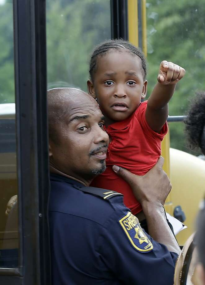 A police officer helps a child off a school bus as busses arrive with students after an incident at Ronald McNair Discovery Learning Academy, Tuesday, Aug. 20, 2013 in Decatur, Ga.  Superintendent Michael Thurmond says all students at Ronald E. McNair Discovery Learning Academy in Decatur east of Atlanta are accounted for and safe Tuesday and that he is not aware of any injuries. (AP Photo/John Bazemore) Photo: John Bazemore, Associated Press