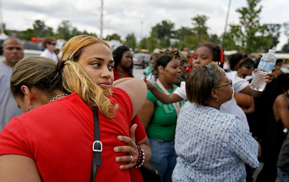 Shanique Worthey, right, is embraced by her mother Daphne Morris, while waiting to be reunited with her son five-year-old son Skyler Worthey as students from Ronald E. McNair Discovery Learning Academy are picked up by loved ones in a Walmart parking lot after they were evacuated when a gunman entered the school, Tuesday, Aug. 20, 2013, in Decatur, Ga. (AP Photo/David Goldman) Photo: David Goldman, Associated Press