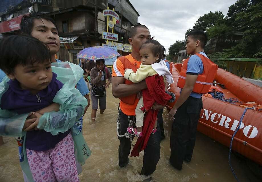 A man and a rescuer carry children to higher grounds as government authorities enforce evacuation at an area flooded due to a swollen river in Marikina city, east of  Manila, Philippines on Tuesday, Aug. 20, 2013. Flooding caused by some of the Philippines' heaviest rains that submerged more than half the capital began receding Tuesday even as authorities evacuated thousands of residents along Manila's overflowing rivers and braced for more chaos in outlying provinces. (AP Photo/Aaron Favila) Photo: Aaron Favila, Associated Press