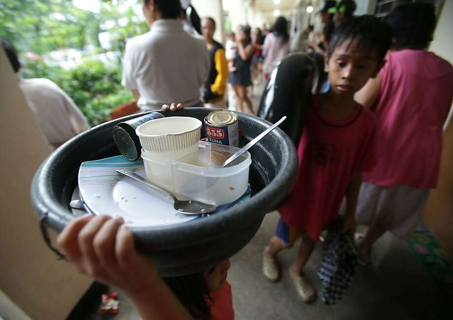 A girl carries used dishes in an evacuation center in Marikina city, east of  Manila, Philippines on Tuesday, Aug. 20, 2013. Some of the Philippines' heaviest rains on record fell for a second day Tuesday, turning the capital's roads into rivers and trapping tens of thousands of people in homes and shelters. The government suspended all work except rescues and disaster response. (AP Photo/Aaron Favila) Photo: Aaron Favila, Associated Press