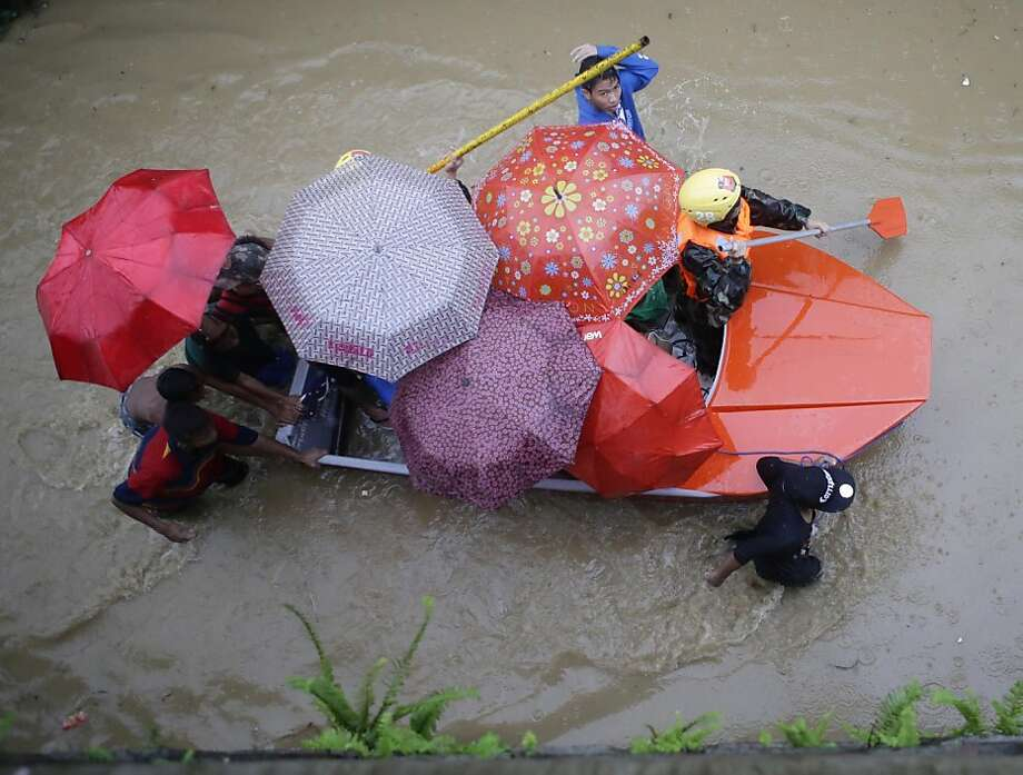 Philippine Army soldiers paddle a boat of residents as they enforce an evacuation following the swelling of Marikina River in Marikina city, east of Manila, Philippines Tuesday Aug. 20, 2013. Flooding caused by some of the Philippines' heaviest rains on record submerged more than half the capital Tuesday, turning roads into rivers and trapping tens of thousands of people in homes and shelters. The government suspended all work except rescues and disaster response for a second day.  (AP Photo/Bullit Marquez) Photo: Bullit Marquez, Associated Press