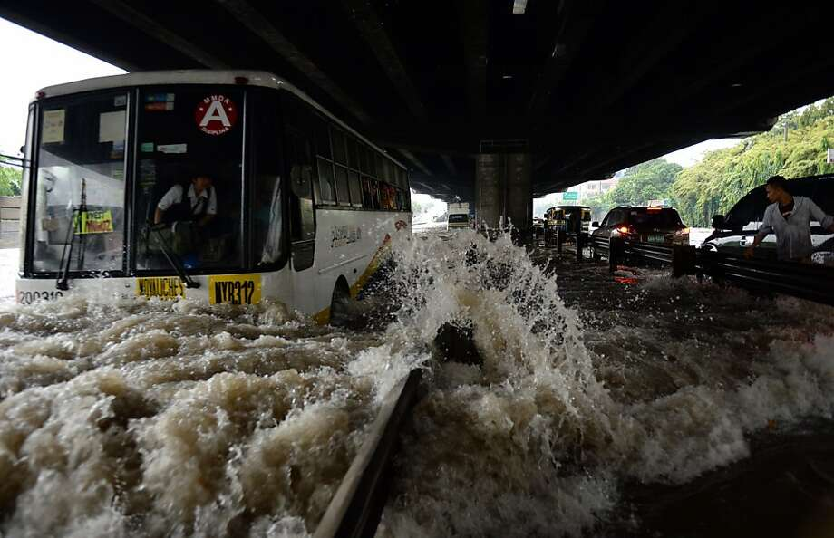 A passenger bus commutes along a flooded highway as heavy rains pummel Manila on August 20, 2013. Flood-battered residents of the Philippine capital and surrounding areas appealed for help August 20 as relentless monsoon rains, which have claimed at least seven lives, submerged more than half of Manila.  AFP PHOTO/TED ALJIBETED ALJIBE/AFP/Getty Images Photo: Ted Aljibe, AFP/Getty Images