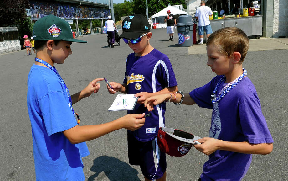 Westport's Christopher Drbal, left, signs autographs for Ean Pokorski, 11, and Ethan Prosser, 11, before team practice at the Little League World Series in Williamsport, Pa. on Tuesday August 20, 2013. Photo: Christian Abraham / Connecticut Post