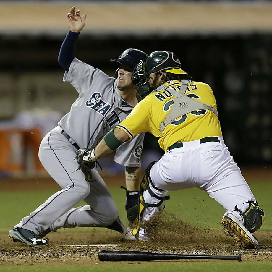 Seattle Mariners' Nick Franklin, left, slides to score past the tag of Oakland Athletics catcher Derek Norris in the eighth inning of a baseball game Tuesday, Aug. 20, 2013, in Oakland, Calif. (AP Photo/Ben Margot) Photo: Ben Margot, Associated Press