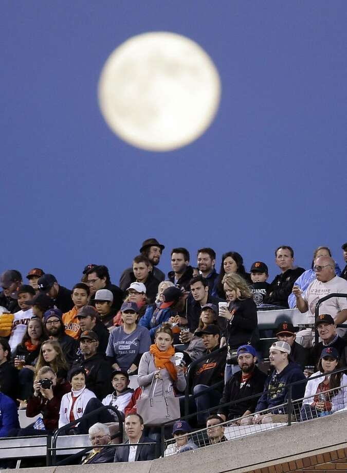 Fans watch a baseball game between the San Francisco Giants and the Boston Red Sox as a full moon rises, Tuesday, Aug. 20, 2013, in San Francisco. (AP Photo/Marcio Jose Sanchez) Photo: Marcio Jose Sanchez, Associated Press
