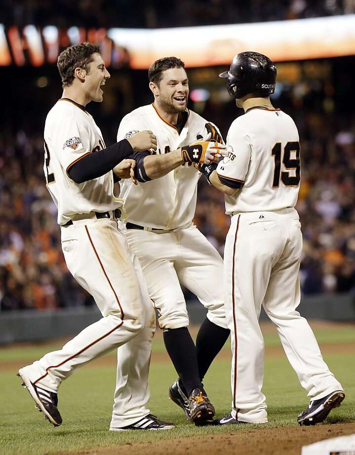 San Francisco Giants' Marco Scutaro (19) is hugged by teammates Brandon Belt, center, and Roger Kieschnick after Scutaro was walked with the bases-loaded and Kieschnick scored the game-winning run during the ninth inning of a baseball game on Tuesday, Aug. 20, 2013, in San Francisco. San Francisco won 3-2.  (AP Photo/Marcio Jose Sanchez) Photo: Marcio Jose Sanchez, Associated Press