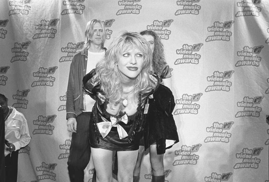 1995: Courtney Love poses for a photo with her band Hole at the press podium backstage. Photo: Catherine McGann, Getty Images / 2013  Catherine McGann