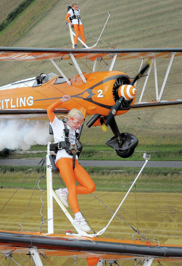 Nine-year-old cousins Rose Brewer (Front) and Flame Brewer (Rear) wingwalk over Rendcomb airfield in Gloucestershire, to become the world's youngest formation wingwalkers on August 21, 2013 in Cirencester, England. The two girls who flew on vintage Boeing Stearman biplanes, were inspired to do so by the plight of Eli Crossley who suffers from Duchenne Muscular Dystrophy. His parents have set up the Duchenne Children's Trust to raise money to research a treatment or cure in time to save Eli's life. Photo: Pool, Getty Images / 2013 Getty Images