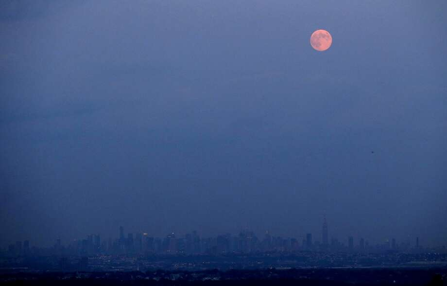 The moon rises over the New York skyline in its full stage under a phenomenon called the blue moon, as seen from West Orange, N.J., Tuesday, Aug. 20, 2013. The moon is better known as a blue moon to scientists. (AP Photo/Julio Cortez) Photo: Julio Cortez, ASSOCIATED PRESS