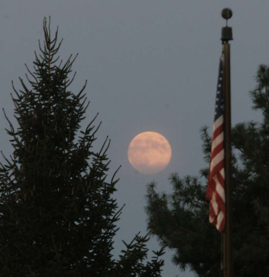 Despite being a blue moon, Tuesday's full moon rises in the evening sky with an orangish/reddish tint as the American flag flies above the soccer field at Kesling Park Tuesday August 20, 2013 in LaPorte, Ind.   (AP Photo/The LaPorte Herald-Argus, Bob Wellinski) Photo: Bob Wellinski, AP