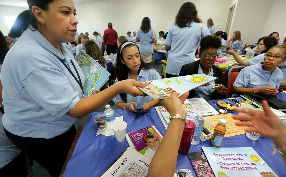 Maria Castro (left), a professional development coach with Pre-K 4 SA, hands out curriculum to staff members. About 500 people applied for 44 teacher and 44 teacher assistant spots. Photo: Bob Owen / San Antonio Express-News