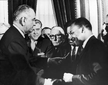U.S. President Lyndon B. Johnson hands a pen to civil rights leader Rev. Martin Luther King Jr. during the the signing of the voting rights act as officials look on behind them, Washington, D.C., August 6, 1965. Photo: Washington Bureau, Getty Images / 2002 Getty Images