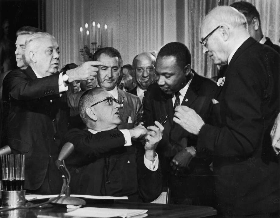US President Lyndon B. Johnson shakes the hand of Rev. Martin Luther King Jr. at the signing of the Civil Rights Act while officials look on, Washington DC. Photo: Hulton Archive, Getty Images / 2003 Getty Images