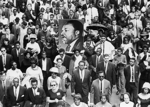A large crowd of mourners follow the casket of Rev. Martin Luther King Jr. through the streets of Atlanta, Georgia. Two men carry a large sign with King's face. Photo: Hulton Archive, Getty Images / Archive Photos