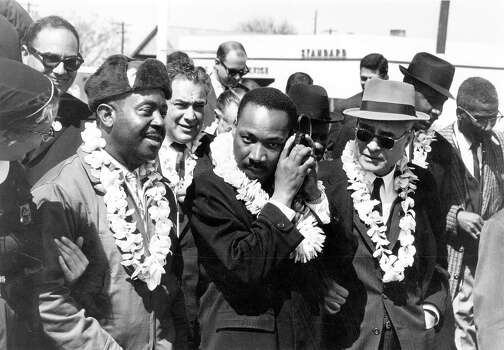 American clergyman and civil rights campaigner Rev. Martin Luther King Jr. listening to the radio whilst leading the Alabama Civil Rights march. On the left is his fellow clergyman and campaigner Ralph Abernathy. Photo: William Lovelace, Getty Images / Hulton Archive