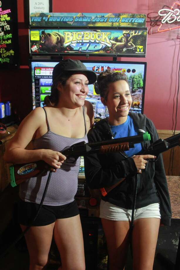 Rose Cordova, left, and Ashley Lopez prepare for the Big Buck Hunter challenge at Stats Sports Bar. Photo: Gary Fountain, Freelance / Copyright 2013 Gary Fountain.